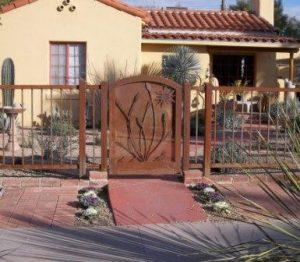 Rusted decorative gate and fence with ocotillo and sun motifs - IF106