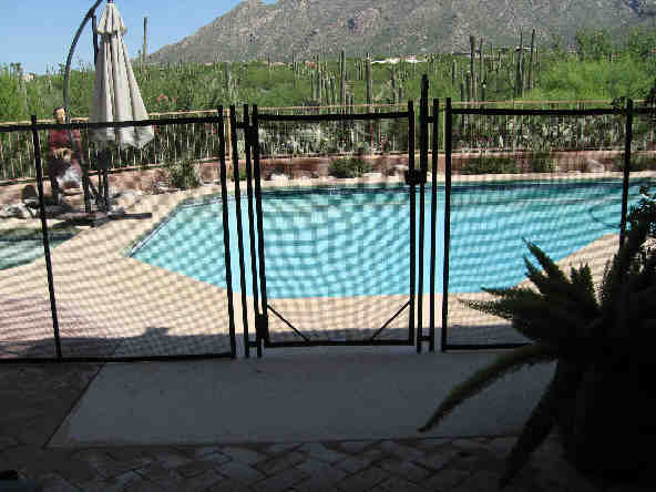 Gate of a mesh pool fence with Tucson Catalinas view | RM104 - Installation by Affordable Fence and Gates