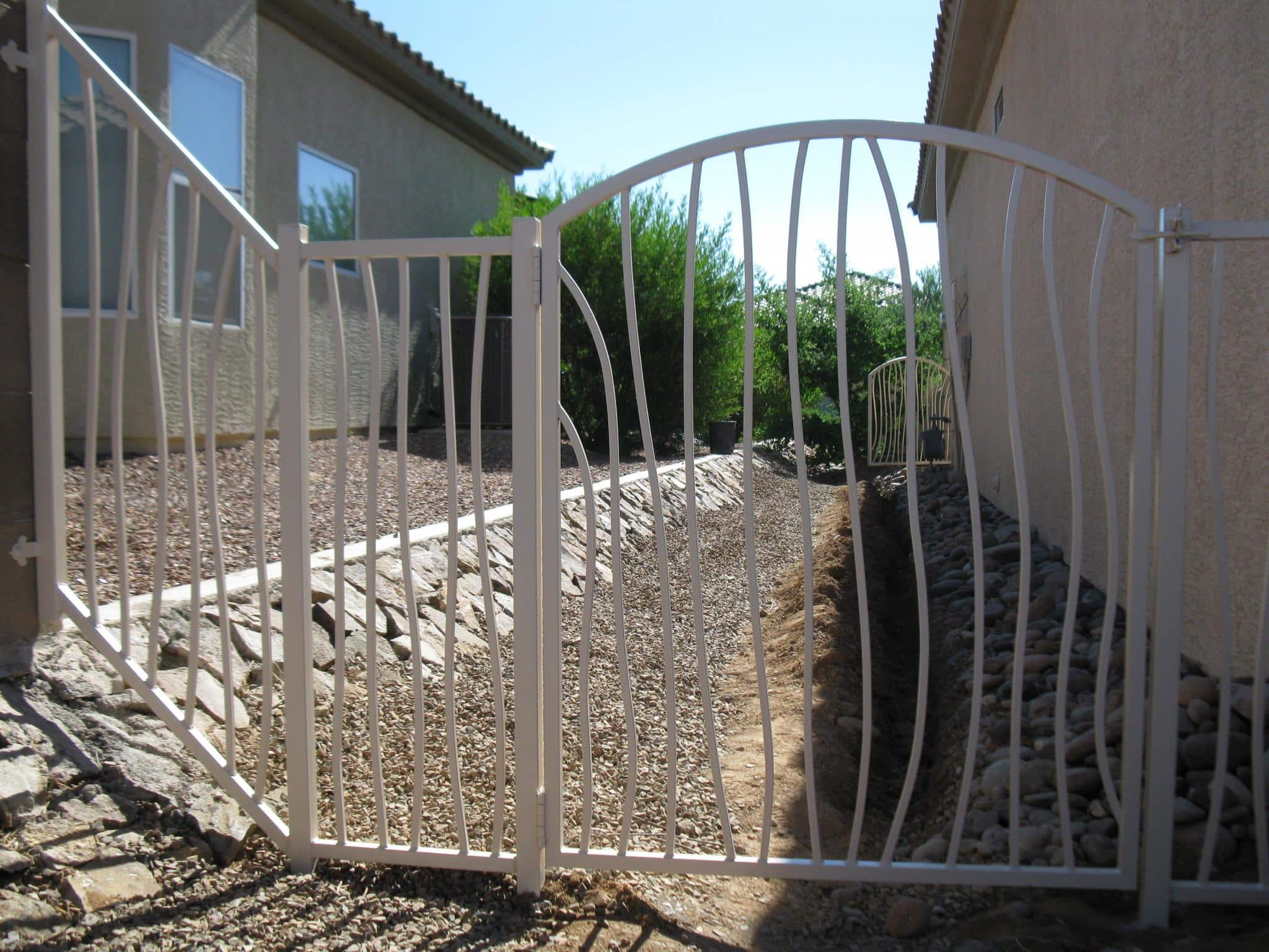 Iron fence and gate with wavy pattern over a water drain channel - Subdivision of Tucson IF228