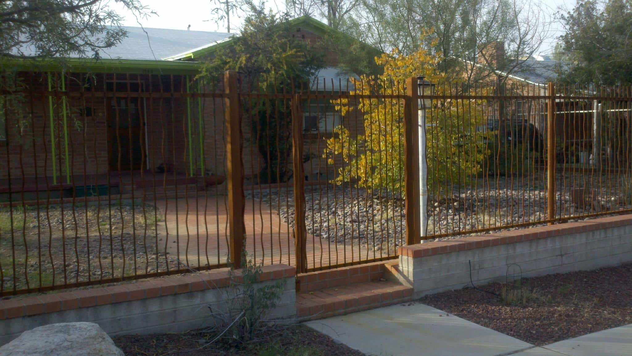 Rusted iron gate and iron fence made in wavy rebar mounted on masonry wall IF306-2 Rebar - Downtown Tucson