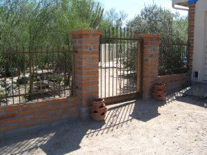 Rust iron gate with scrolls and spears, anchored to brick posts IF220-2