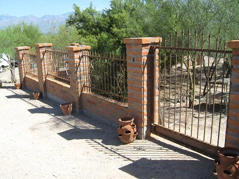 Rust iron fence with spears and swirls, anchored to masonry posts - Installed in Tucson IF220