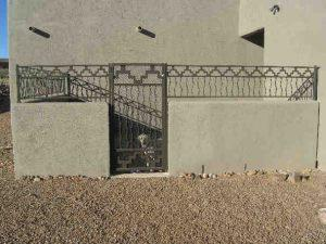 Short wall-mounted wrought iron fence and gate with southwestern motif IF213