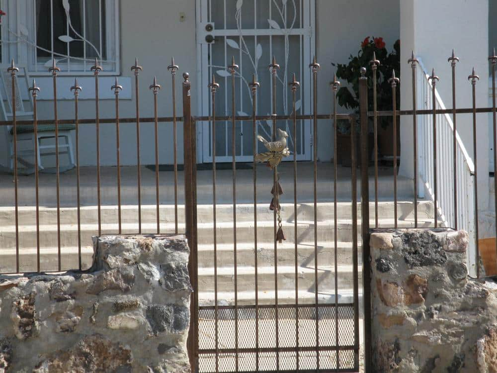 Wrought iron gate and fence with spear tips and bird decorative motif IF211