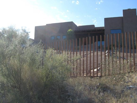 Pipe fence with rust patina installed on graded terrain IF401 - Foothills Tucson