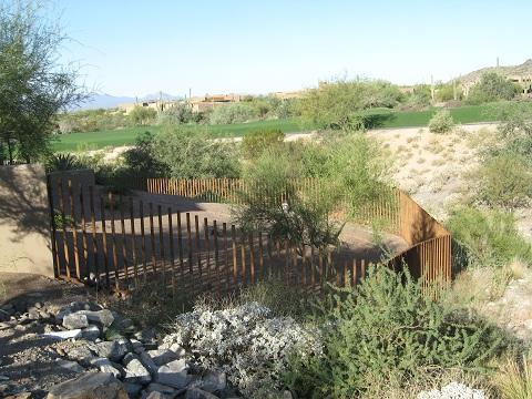Rusted Pipe Fence IF403 installed on hilly terrain in Tucson