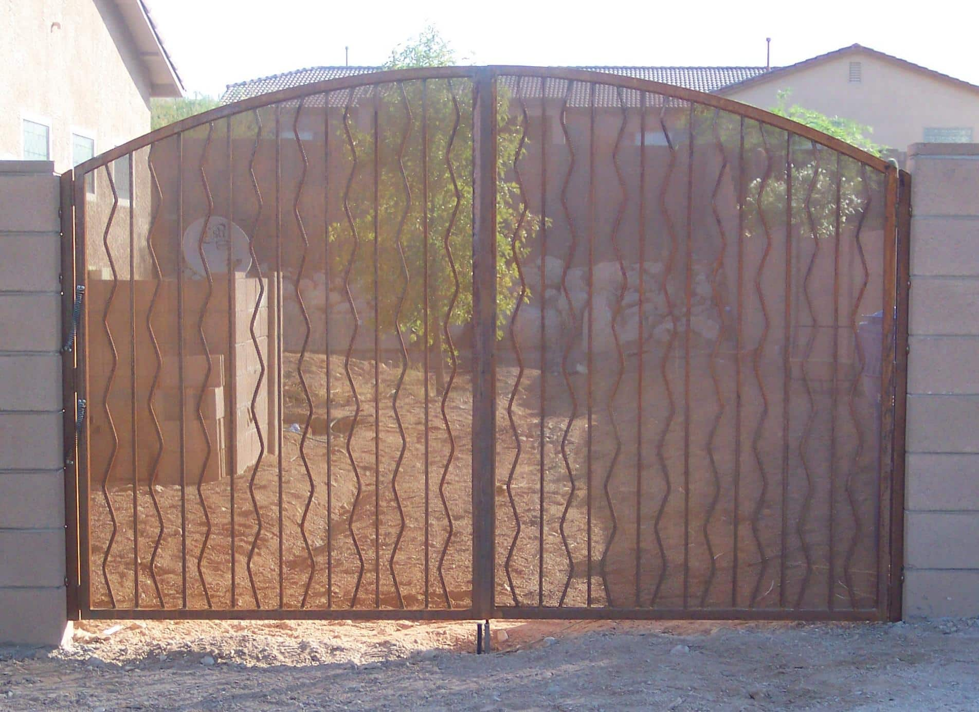 Arched top double wrought iron gate with alternate wavy pattern and perforated metal backing Tucson IG016