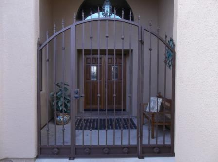 Arched top wrought iron enclosure with spear points and floral motifs on kick plate made in Tucson IG084
