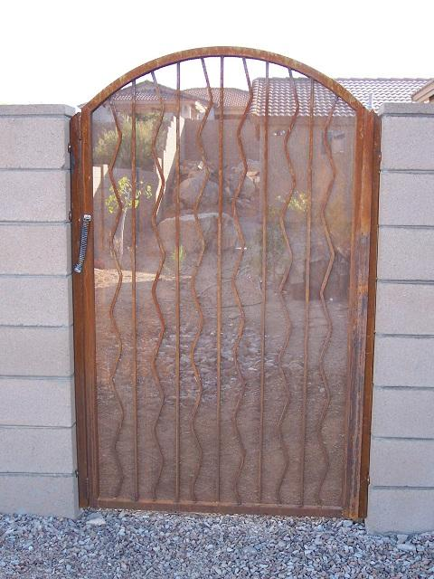 Arched top wrought iron gate with alternate wavy pattern, perforated metal backing and spring-loaded closure mechanism IG005