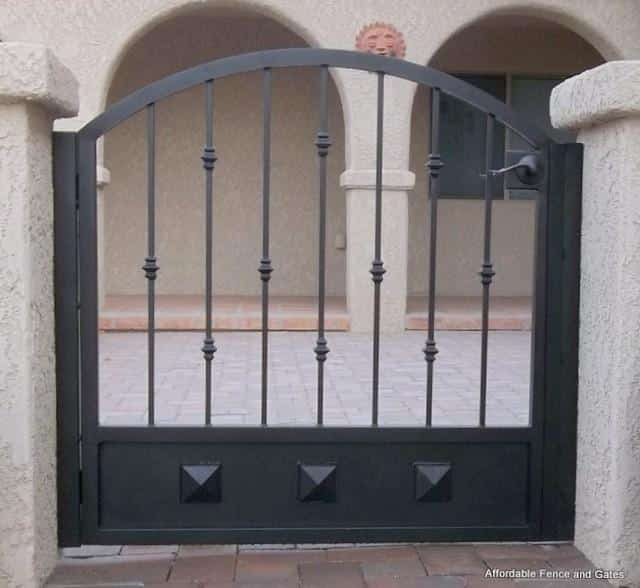 Arched top wrought iron gate with knuckles and clavos on the kick plate IG089