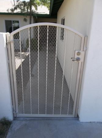 Arched top wrought iron gate with expanded steel backing and white finish IG086