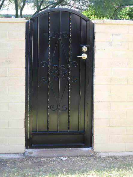 Black wrought iron gate with alternate twisted pattern, scroll work, and solid steel sheet backing made in Tucson IG053