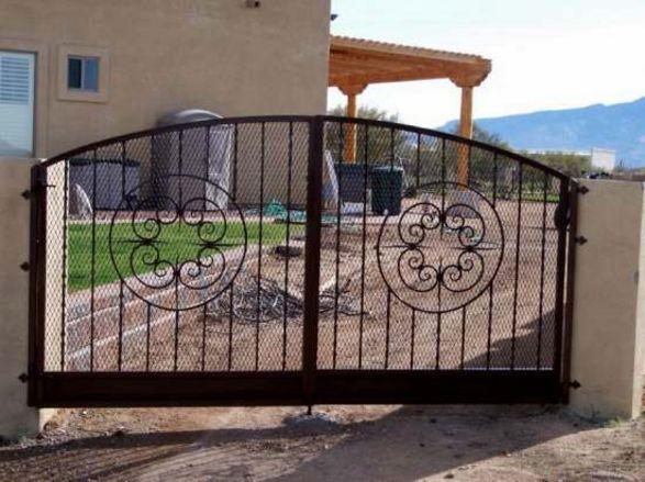 Installed Ornamental Iron Gate with Scroll Work and Large Bottom Rail