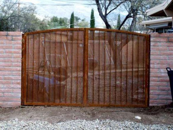 Rust finish arched-top wrought iron gate with perforated metal backing made in Tucson IG002