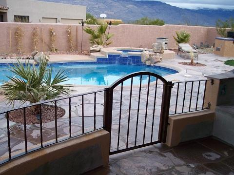 Small arched top wrought iron gate and fence with twisted pattern enclosing a pool IG078