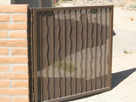 Wrought iron gate with alternate wavy pattern and perforated metal backing Tucson IG004