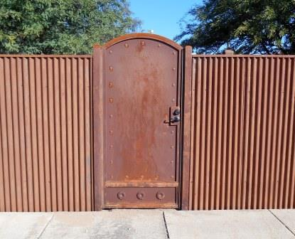 Sheet Steel Gate   Affordable Fence & Gates   Signature Ironworks   Corrugated Steel Gate   Rusty Corrugated Steel Gate   Natural Rust Corrugated Steel Gate   Arch   Rivets   Clevos   Handle   Court Yard Gate   Flower Detail   Natural Rust Color