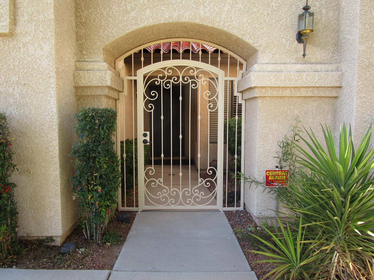 Porch enclosure with security door decorated with swirls and knuckles 7017 E - Made in Tucson