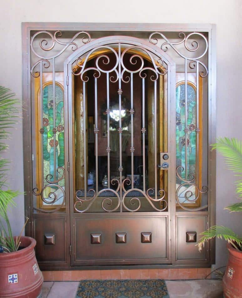 Security enclosure with scroll work, knuckles and other decorative motifs on security door, kick panel and side panels 7010 E - Made in Tucson