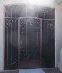 Iron security enclosure with arched security door ornamented with swirls and knuckles - Diamond ornements on bottom plate - 7007 E - Made in Tucson