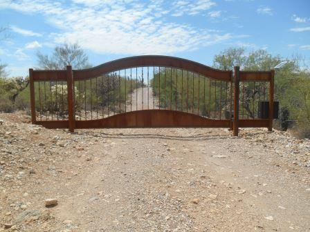 Solar-powered arched top automatic driveway gate with rusted metal finish and side panels | AG33