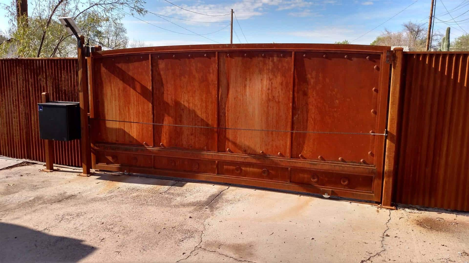 Sheet Steel Gate   Affordable Fence & Gates   Signature Ironworks   Corrugated Steel Gate   Rusty Corrugated Steel Gate   Natural Rust Corrugated Steel Gate   Arch   Rivets   Clevos   Automatic Driveway Gate   Flower Detail   Natural Rust Color