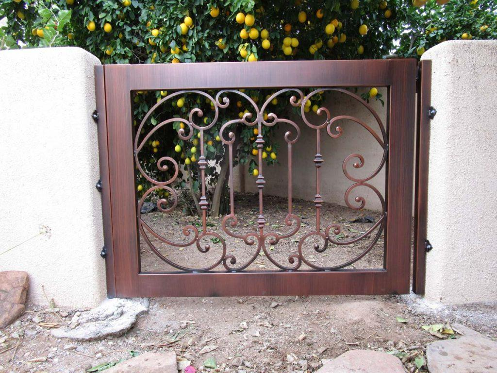 Ornamental iron gate with scroll design and a powder coated faux finish