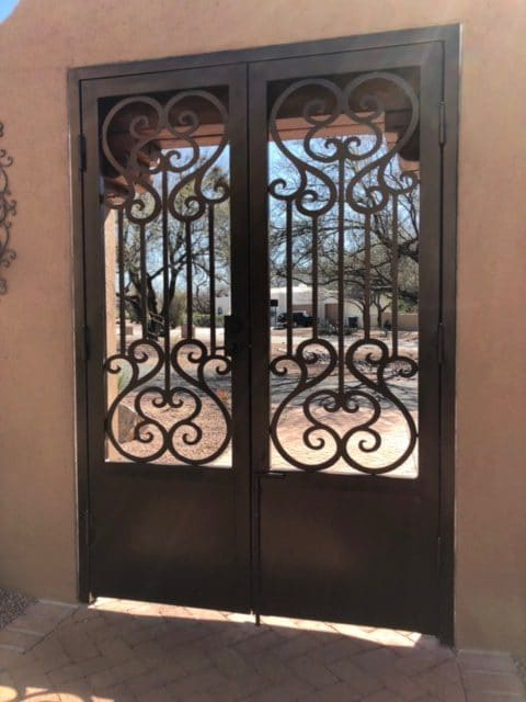 Double ornamental iron gate with scrolls and large kick plate