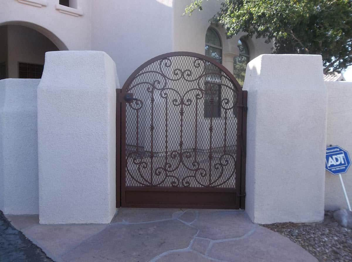 Arched-top wrought iron gate with scroll work, knuckles on pickets, and expanded steel backing 100 0791 - Made in Tucson