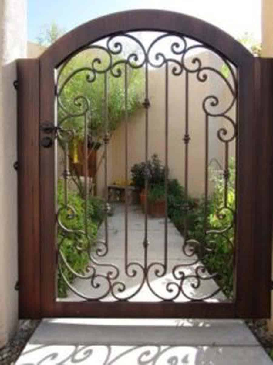 Arched wrought iron gate with scroll work and knuckles with a bronze finish 858 IG
