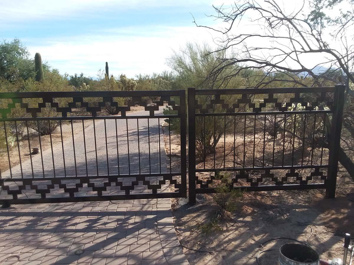 Automatic driveway gate with straight pickets and a geometric southwestern motif. Short side fence 150206