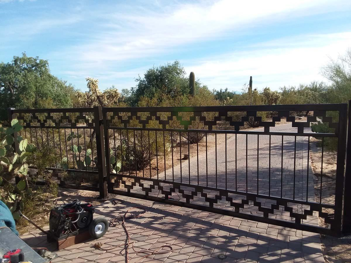 Automatic driveway gate with straight pickets and a geometric southwestern motif. Short side fence 150209(0)