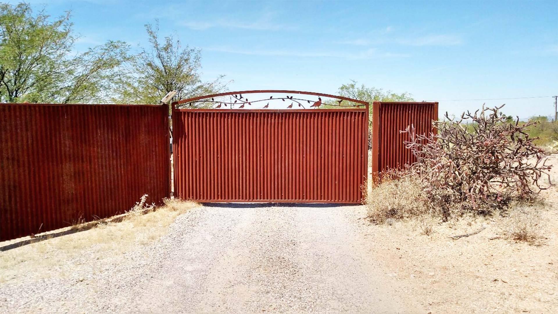 Corrugated Steel Gate | Signature Ironworks | Affordable Fence & Gates | Signature Ironworks | Corrugated Steel Gate | Rusty Corrugated Steel Gate | Natural Rust Corrugated Steel Gate | Arch | Desert Scene | Driveway Gate | Auto Gate | Natural Rust Color