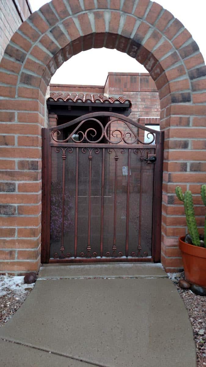Courtyard wrought iron gate with arched top and scroll work 082046514