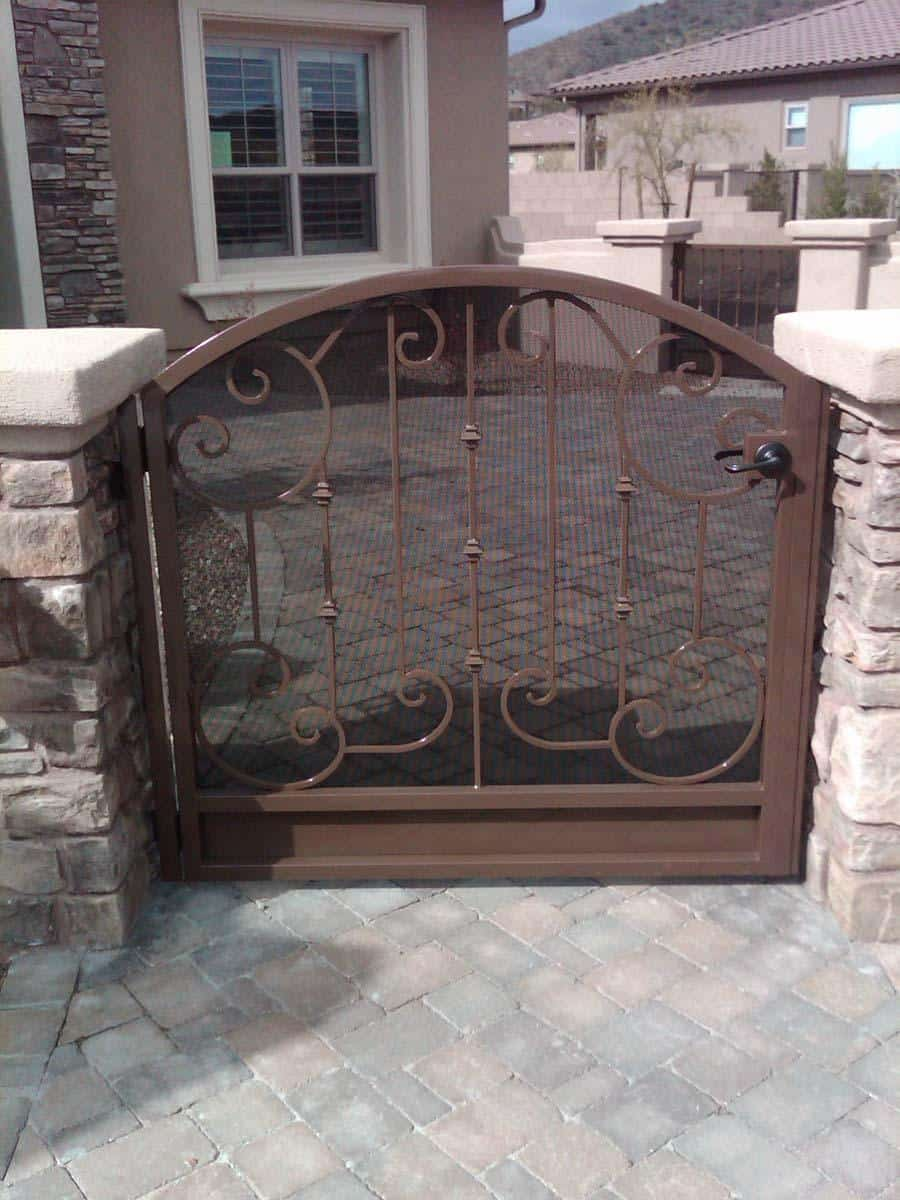 Courtyard wrought iron gate with perforated metal backing and scroll work