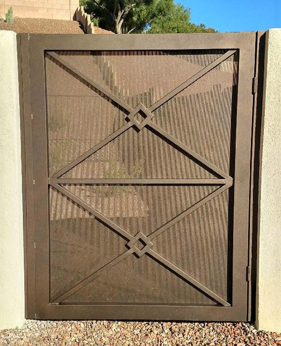 Courtyard wrought iron gate with perforated metal backing and geometric motif 082724287 HDR