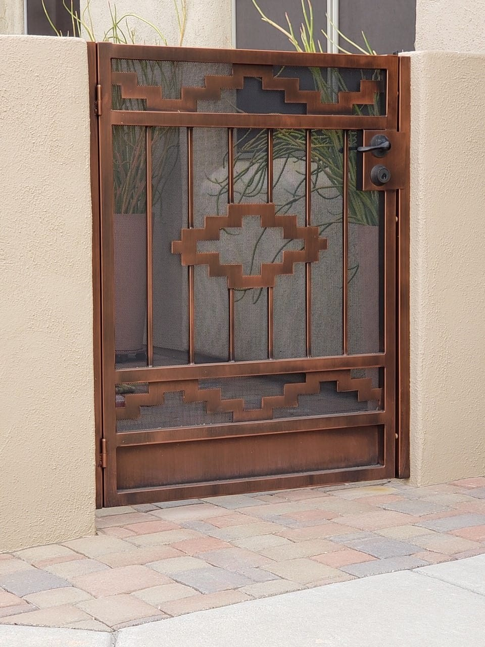 Custom wrought iron gate with southwestern decorative motifs and perforated metal backing plate 53131