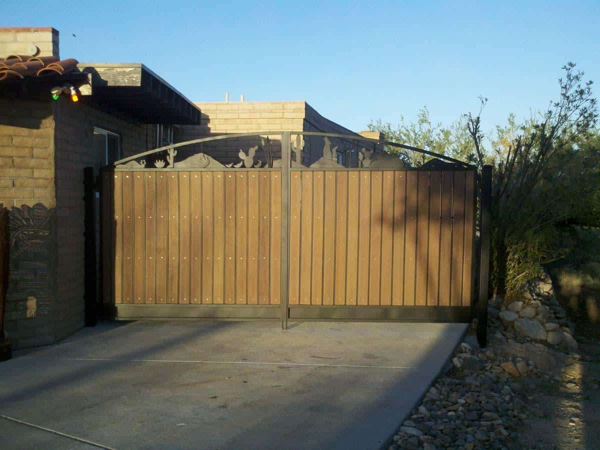 High double driveway gates with iron-wood paneling on a southwestern theme on the arched top (wolves, cacti, saguaro, agave, mountains) 055759431