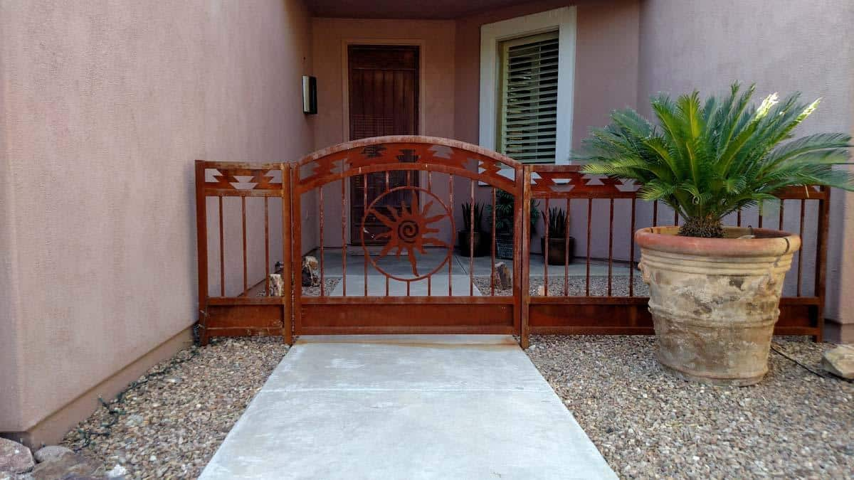 Southwestern style wrought iron gate and fence with sun cutout and rust patina 102300965