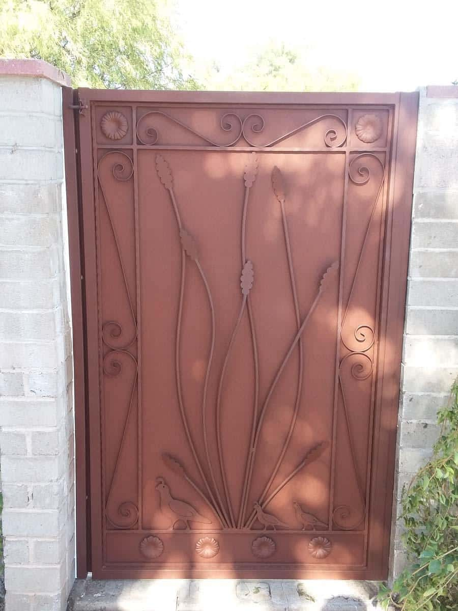 Tucson: Wrought iron gate with metal backing and decorative motifs: ocotillo, quails, scrolls and flowers on the kick plate 124939
