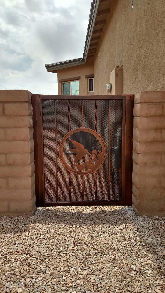 Wrought iron garden gate with hummingbird decorative motif over perforated metal plate 132801070 HDR