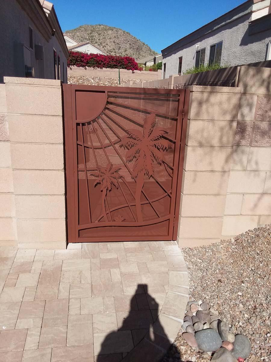 Wrought iron gate with perforated metal backing plate and decorative cutouts (palm trees, sun and mountains) installed in Tucson 133632